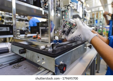 MEDOLLA, ITALY-OCTOBER 17, 2012: Hands with gloves assembling a medical device on a factory line, at the Gambro factory, Italian division.
