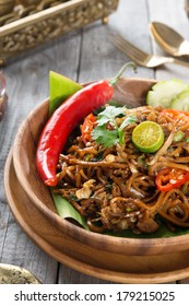 Mee goreng mamak or mi goreng, Indonesian and Malaysian cuisine, spicy fried noodles with wooden dining table setting. Fresh hot with steamed smoke.
