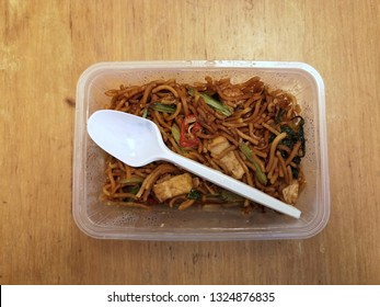 'Mee Goreng' in a transparent plastic container with a white spoon, served on a wooden table for breakfast. selected focus.
