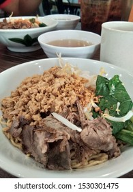Mee kolok from Malaysia is a type of Sarawakian noodle dish tossed in transparent sauce. It served with choy sum vegetables, shallots, fish sauce, soy sauce and chicken bouillon.