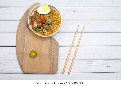 Mee Rebus in the bowl  with chopsticks on white table This dish is made of noodles ,vegetable,egg with a spicy .