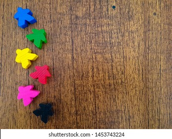 Meeple. Wooden background. Colored token. Funny game tokens.