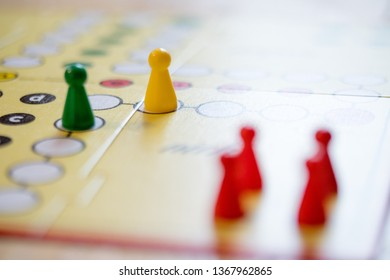 Meeples on a board, ready for playing a parlor game, ludo