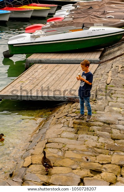 MEERSBURG, GERMANY - AUG 6, 2017: Boy in a harbour of Meersburg, a town of Baden-Wurttemberg in Germany at Lake Constance.
