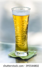 MEERU, MALDIVES - DECEMBER 14, 2012: A glass of cold Carlsberg beer in a glass on the table
