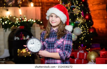 Meet Christmas holiday. Festive atmosphere christmas day. New year countdown. Counting time. Few minutes till new year. Magic moment is coming. Christmas almost here. Girl santa claus hat and clock.