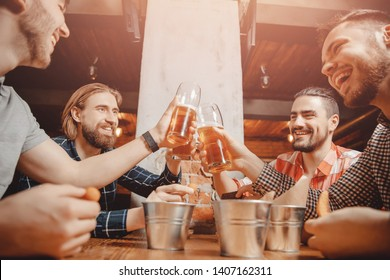 Meet friends of men in beer bar, happy smiles on your face. Concept celebration victory of sports team.