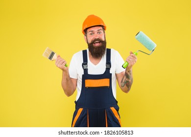 Meet natural art. Decorator hold paint roller and brush. Happy painter yellow background. Color man in working clothes. Paint work. Applying lacquer. Renovation and repair. Renewal and redecorating.