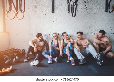 Meet up on the mat. Beautiful young womens and mans in sportswear discussing something with smile and using smartphone while sitting on exercise mat at gym