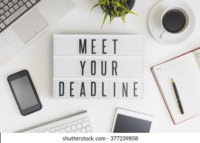 Meet your deadline words on office table with computer, coffee, notepad, smartphone and digital tablet