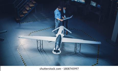 Meeting of Aerospace Engineers Work On Unmanned Aerial Vehicle / Drone Prototype. Aviation Experts have Discussion. Industrial Facility with Aircraft Capable of GPS Surveillance and Military Missions