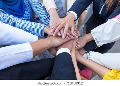 A meeting of Arab and Asian employees to work together as a team for success. The hand of the group represents the teamwork. It makes people in the company confident and work happily.