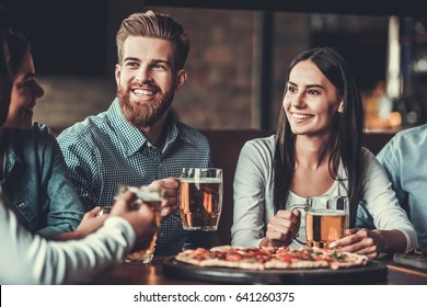 Meeting with the best friends. Handsome friends smile and talk while relaxing in pub with beer and pizza.
