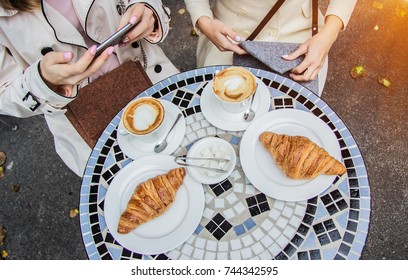 Meeting of best friends. Top view of beautiful french women sitting in french vintage cafe. Woman using smart phone. Friends drinking fresh coffee with croissants in cafe. French breakfast concept.