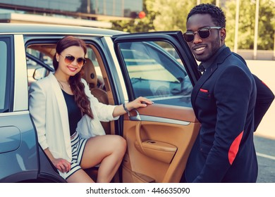Meeting of black casual man and business woman near a car.