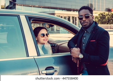 Meeting of black casual man and caucasiand business woman near a car.