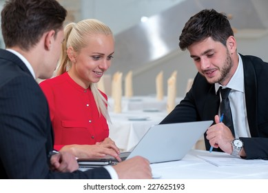 Meeting business clients. Two successful and confident businessmen and one stylish businesswoman are sitting at the table with laptop and discussing the business project start