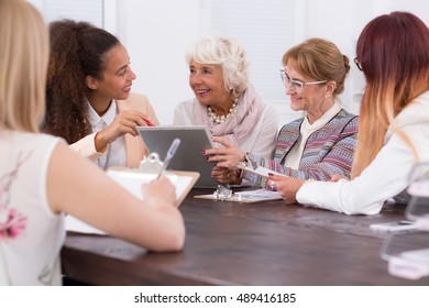 Meeting of businesswomen sitting at one desk in the work office