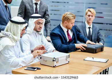 Meeting of caucasians and arabian. Sitting on table with cases, caucasian men in suits, sheikhs in white suits. America and saudi arabia, dubai
