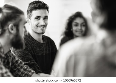 Meeting at college  . A working students group meets to work their project. Focus on a young man looking at camera. Black and white