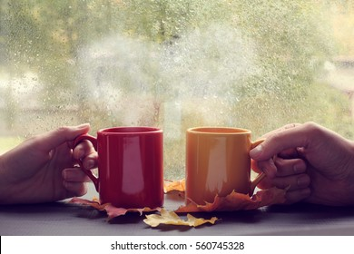 meeting couples in love during a coffee break against the window with rain drops / romantic love story