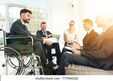 Meeting of disabled people in a bright room with wide windows. Men in wheelchairs businessmen. Meeting of disabled people in business suits.