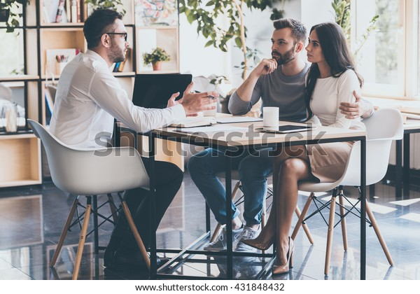 At the meeting with finance advisor. Concentrated young couple bonding to each other and listening to their financial advisor sitting at the desk in front of them