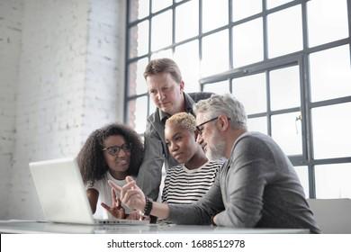 réunion de cinq personnes au bureau avec un ordinateur