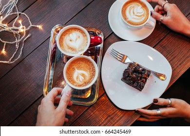 Meeting friends in a cafe, warm, music, coziness. Friends drink coffee and eat dessert, tell their news.