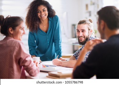 Meeting at the office. a beautiful young black woman discusses with her colleagues sitting around the table
