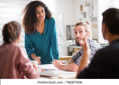 Meeting at the office of a modern, multi-ethnic company. a beautiful young black woman talking to her colleagues sitting around the table.