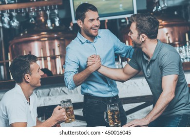 Meeting old friends. Three cheerful friends meet each other in beer pub