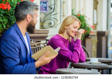 Meeting people with similar interests. Man and woman sit cafe terrace. Literature common interest. Find girlfriend with common interest. Guide to dating. Flirt and date. Girl interested what he read.