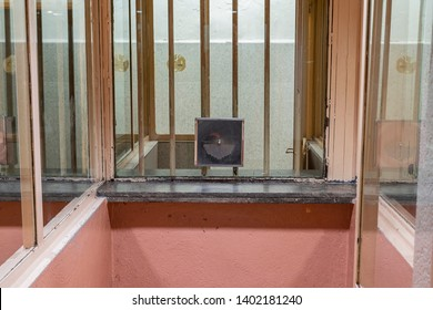 Meeting place in prison with intercom. Room divided in half by a lattice and glass. Place to meet prisoners with visitors.