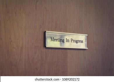 Meeting in progress sign on a conference room door