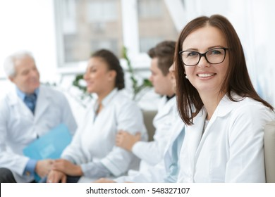 Meeting of the pros. Beautiful mature woman doctor smiling to the camera her medical team during their meeting on the background copyspace happiness professionalism hospital teamwork medicine concept
