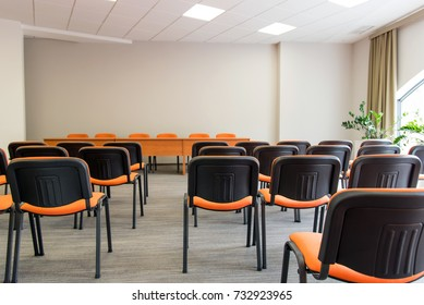 Meeting room interior.  Front view of rows of orange chairs standing in an auditorium. Seats in an empty conference room. Huge Hall interior with carpet and lights as conference hall in luxury hotel.