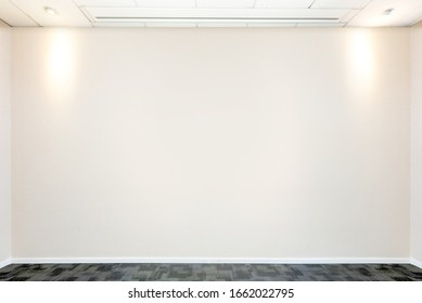 Meeting room with lights and empty wall in the office building