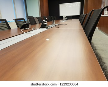 Meeting room with long table, chairs, whiteboard and speakerphone in a corporate office