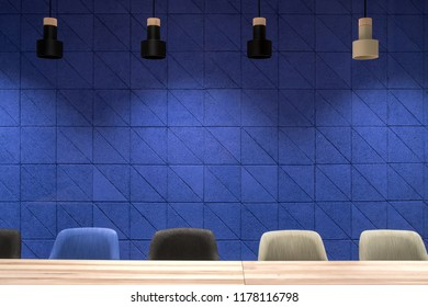 Meeting room in a luminous office with a textured blue wall. There are wide wooden tables with multicolor chairs, hanging dark and light lamps. Horizontal.
