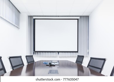 Meeting room with table chair and projector screen in modern office