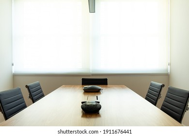 meeting room with wooden table and black chairs with window in the background