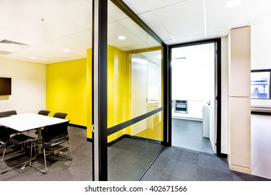 Meeting room with yellow walls and hallway and the lights on