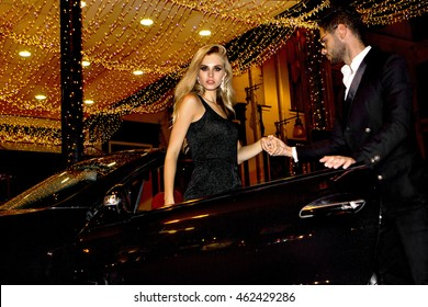 Meeting stars on the red carpet. Couple in luxury car. Night life.