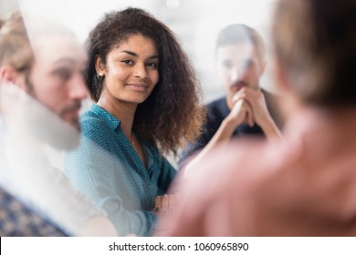 Meeting at the startup office . A working group meets to study a new project. Focus on a beautiful young black woman looking at camera