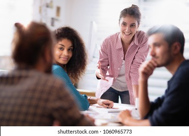meeting at the startup office. A young woman leads a multi-ethnic working group