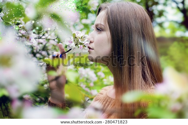 The meeting with summer, the woman smells flowers on an apple-tree