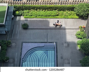 Meeting in the sunny day. Business taking at balcony between three people. Outdoor seating near swimming pool. Hotel balcony with a little green garden.