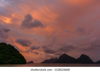 Meeting the sunset at sea. Las Cabanas beach - El Nido Philippines, Palawan. The sun sets in the sea. Tropical islands in the sea.