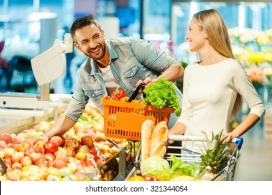 Meeting in supermarket. Beautiful young couple choosing products in supermarket and looking at each other with smile